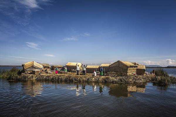 An Uros Island family greets visitors, Lake Titicaca, Peru
