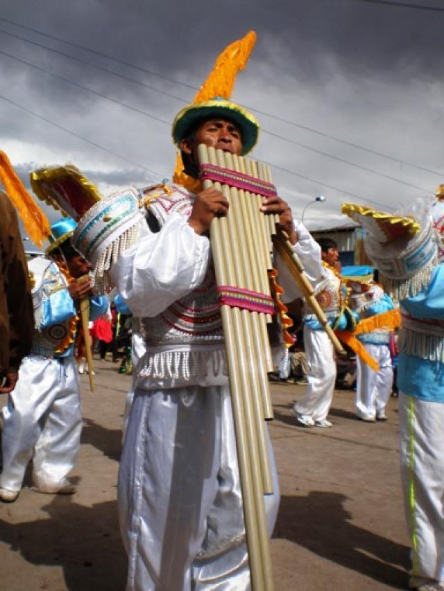 A man plays a large Peruvian flute during the fesivities of La Candelaria in Puno, Peru