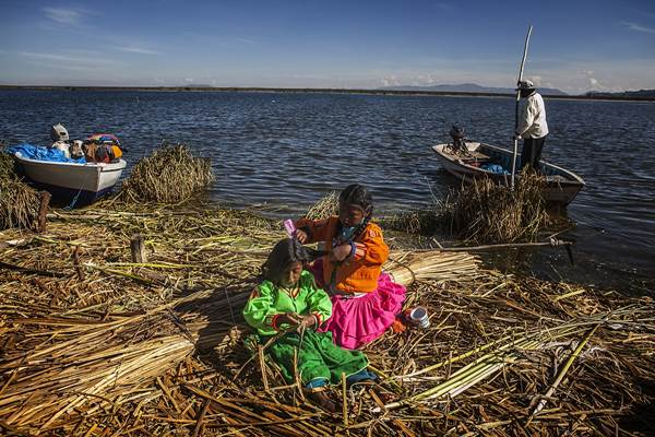 Two girls of the Floating Islands of Uros braid their hair in the traditional style, Lake Titicaca, Peru